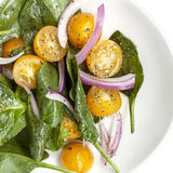 Spinach Salad with Yellow Cherry Tomatoes and Red Onion. Overhead view, on white plate royalty free stock photography