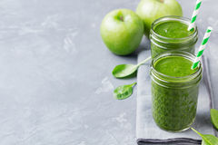 Spinach smoothie Healthy drink in glass jar on grey stone background. Copy space Stock Photo