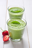Spinach smoothies. In glass served with strawberry on a wooden background Stock Photography