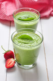 Spinach smoothies. In glass served with strawberry on a wooden background Stock Photos