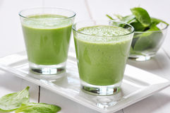 Spinach smoothies. In glass on a wooden background Stock Photos