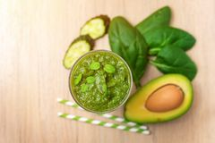 Spinach smoothies. Healthy green juice with ingredients on light wooden table. Top view.  stock photo