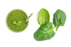 Spinach smoothies. Healthy green juice iwith spinach leaves solated on white background. Top view.  royalty free stock image