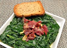 Spinach stew with ham and garlic stock photos