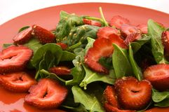 Spinach and Strawberry Salad. This closeup is of a fresh spinach and strawberry salad on a red plate.  Also has sesame seeds and garlic for a delicious side Royalty Free Stock Photography