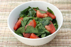 Spinach Tomato Salad with Salt and Coconut Oil in a White Bowl. Closeup of Spinach Tomato Salad with Salt and Coconut Oil in a White Bowl on a cotton fiber stock image