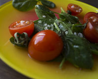The spinach and tomatoes. Spinach and tomatoes with salt on the yellow plate.n Royalty Free Stock Photo