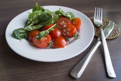 The spinach and tomatoes. The spinach and tomatoes on a white plate.n Stock Image