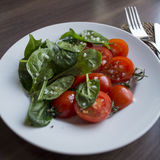 The spinach and tomatoes. The spinach and tomatoes on a white plate.n Stock Photo