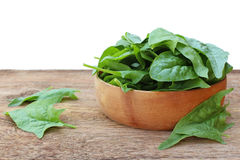 Spinach in wooden plate on an old wooden background isolated on Royalty Free Stock Photo