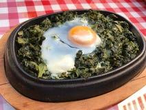 Spinaci della casseruola con l'uovo sulla tovaglia rossa e sulla superficie di legno Fotografia Stock