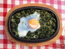Spinaci della casseruola con l'uovo sulla tovaglia rossa e sulla superficie di legno Fotografie Stock Libere da Diritti