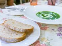 Spinash krämsoppa och två bröd Royaltyfria Bilder