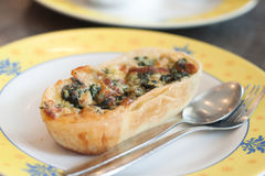Spinash quiche on dish with fork and spoon Stock Photo