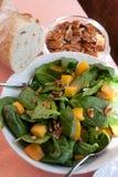 Spinat-Salat mit Pekannüssen, Pfirsichen und frischem Brot Lizenzfreie Stockfotos