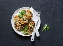 Spinatszucchinistückchen - köstliche vegetarische Snäcke, Aperitifs, Frühstück auf einem dunklen Hintergrund lizenzfreies stockfoto