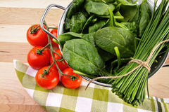 Spinaziebladeren met tomaten en zeef Stock Foto's