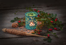 Spindle, a branch of wild rose and lantern Royalty Free Stock Image