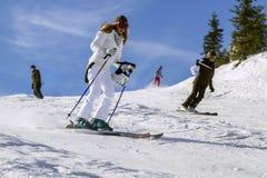 SPINDLERUV MLYN, 2013年3月03日的捷克 在山的倾斜的年轻活跃妇女滑雪在一个冬天晴天 免版税库存图片