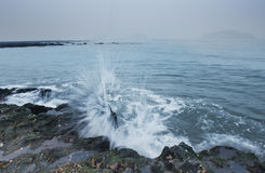 The spindrift. The waves on the rocks, splashed white spray Stock Photo