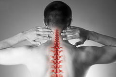 Spine pain, man with backache and ache in the neck, black and white photo with red backbone. On gray background royalty free stock photo