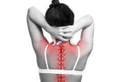 Spine pain, woman with backache and ache in the neck, black and white photo with red backbone. On gray background royalty free stock images