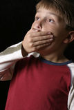 Spine Tingling. Boy with hand over his mouth Royalty Free Stock Photos