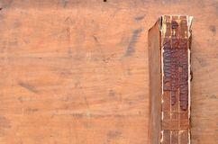 Spine of a vintage leather bound book on old rustic wood. Crumbling Spine of a vintage leather bound book on old rustic wood Royalty Free Stock Photos