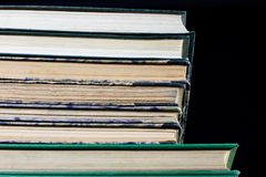 The spines of old books lying on the stack. Books stacked on an. Old table. Black background Royalty Free Stock Photography