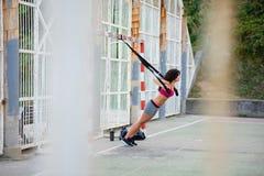Spinga aumenta l'allenamento di forma fisica con le cinghie del trx Immagini Stock
