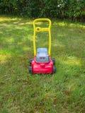 Spinga il giocattolo della falciatrice da giardino sull'erba in un giardino Nessuna gente Fotografie Stock Libere da Diritti