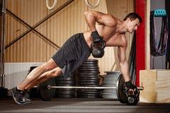 Spinga verso l'alto sull'uomo dei kettlebells che fa l'addestramento di forma fisica Immagine Stock