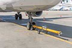Spingendo l'aereo indietro il carretto rimorchia il tracktor sul carrello di atterraggio anteriore del telaio Immagini Stock Libere da Diritti