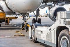 Spingendo l'aeroplano indietro il carretto rimorchia il tracktor sul carrello di atterraggio anteriore del telaio Fotografia Stock