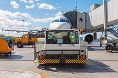 Spingendo l'aeroplano indietro il carretto rimorchia il tracktor sul carrello di atterraggio anteriore del telaio Servizio e prep Immagini Stock Libere da Diritti