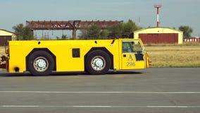 Spingitoio del camion di rimorchio dell'aeroplano che guida sull'aerodromo archivi video