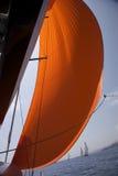 Spinnaker anaranjado en el viento Imagenes de archivo