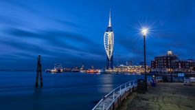 Spinnaker Tower Blues. Smooth waters and long cloud trails accentuate the Spinnaker Tower and Gun Wharf from Old Portsmouth at blue hour Stock Image