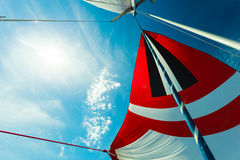 Spinnaker with uphaul, blue sky in background. Spinnaker with uphaul on sail boat, blue sky in background. Marine sailing objects concept Stock Image