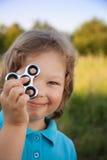 Spinnare i handen av ett barn som ler i naturen på en sommar Royaltyfria Foton