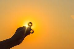 Spinnaren roterar i handen för man` s mot bakgrunden av solen Copyspace Royaltyfria Bilder