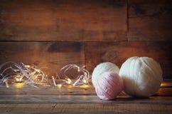 Spinnen Sie Bälle der Wolle auf Holztisch mit garlan Goldlichtern Stockbild