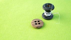 Spinnen Sie mit Knopf und Nadel auf grüner Tabelle Lizenzfreies Stockfoto