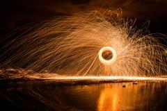 Spinnende Stahlwolle-Funken, die Wasserbecken reflektieren stockfotos