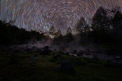 Spinnende sterren en warm waterdamp op rotsen bij nacht stock afbeelding