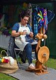 Spinnende Wolle der Frau am traditionellen Spinnrad Lizenzfreie Stockfotos
