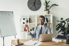 spinnender Fußball des jungen Geschäftsmannes auf Finger lizenzfreie stockbilder
