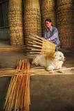 Spinnender Korb der älteren Frau eigenhändig mit einem Hund, der sich hinlegt Lizenzfreie Stockfotos