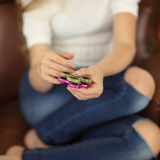 Spinner concept. two spinners green and pink in child`s hands closeup indoors playing girl stock image