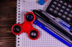 Spinner en verschillende kantoorbehoeften op houten bureau Hoogste mening stock afbeelding